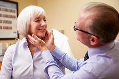 Cosmetic surgeon examining senior female client in office Kuvituskuvat