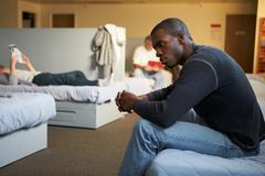 Men sitting on beds in homeless shelter Stock Photos