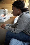 women sitting on beds in homeless shelter - stock photo