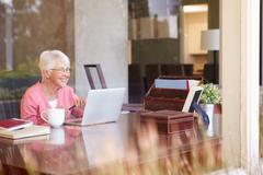 view of senior woman using laptop through window - stock photo