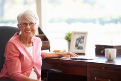 senior woman writing memoirs in book at desk - stock photo