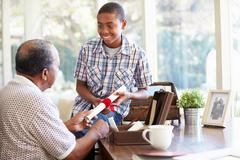Grandfather showing document to grandson Stock Photos