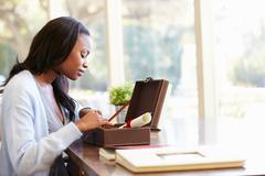 Woman looking at document in keepsake box on desk Stock Photos