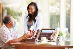 Senior father discussing document with adult daughter Stock Photos