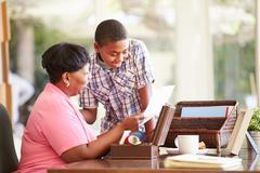 Grandmother showing document to grandson Stock Photos