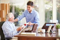 Grandfather showing document to teenage grandson Stock Photos
