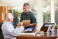 Senior father discussing document with adult son Stock Photos