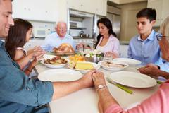 Multi-generation family saying prayer before eating meal Stock Photos
