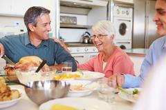 Multi-generation family sitting around table eating meal Stock Photos