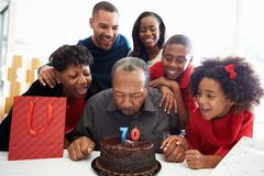 Family celebrating 70th birthday together Stock Photos