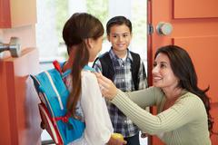 Mother saying goodbye to children as they leave for school Stock Photos