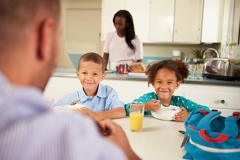 Family eating breakfast at home together Stock Photos