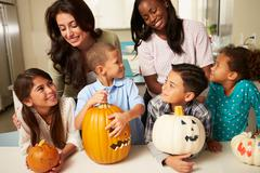 Mothers and children making halloween lanterns Stock Photos