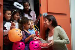 Children going trick or treating with mother Stock Photos