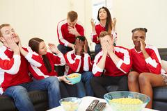 Group of sports fans watching game on tv at home Stock Photos