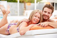 Young couple on holiday relaxing by swimming pool Stock Photos