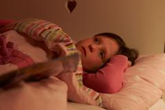 Worried girl lying in bed awake at night Stock Photos