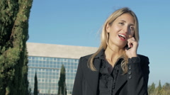 Young and attractive businesswoman talking at the phone: using mobile phone Stock Footage
