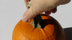 Hand opens and closes the top of a small orange pumpkin 1247 loop Stock Footage