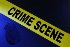 Stock Photo of yellow crime scene tape on blue background with fingerprint
