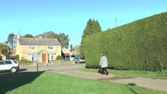 Woman walking small dog in an old English village - 1 Stock Footage