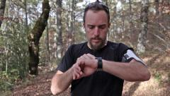 Runner looking smartwatch while running Stock Footage