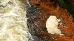 Fast full-flowing water between sandstone rocks, orange foamy sediments Stock Footage