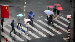 People crossing the intersection during the rain in Shanghai, China Stock Footage