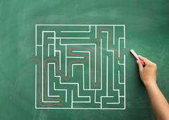 Hand solving maze drawn on blackboard Stock Photos