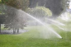 gardening. lawn sprinkler spraying water over green grass in garden - stock photo