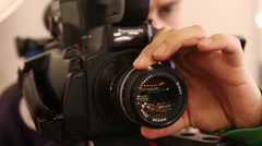camcorder operator adjusts the focus of the lens - stock footage