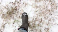 Feet in rubber boots walk on snow-covered field, then stop, then go further Stock Footage