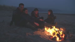Family Sitting By Fire On Winter Beach Stock Footage