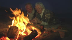 Senior Couple Sitting By Fire On Winter Beach Stock Footage