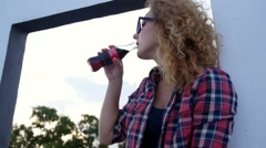 Portrait of Young Curly Beautiful Woman Drinking Soda from a Glass Bottle. Stock Footage