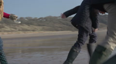 Multi Generation Family Running On Winter Beach With Dog Stock Footage