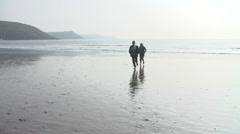 Senior Couple Running On Beach In Slow Motion Stock Footage