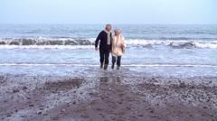 Slow Motion Shot Of Senior Couple Running Along Winter Beach Stock Footage