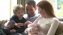 Family Sitting On Sofa With Newborn Baby Stock Footage