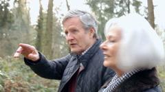 Senior Couple Walking Through Winter Countryside Stock Footage