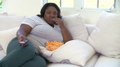 Overweight Woman At Home Eating Snacks And Watching TV Stock Footage