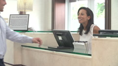 Couple Checking In At Hotel Reception Using Digital Tablet Stock Footage