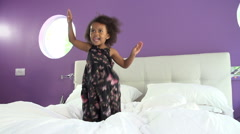 Cute Little Girl Jumping On Parent's Bed - stock footage