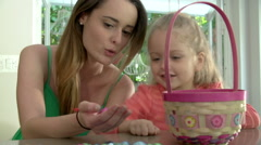 Mother And Daughter With Chocolate Easter Eggs And Basket - stock footage