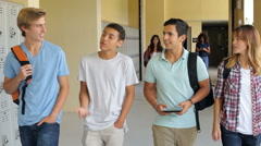 Group Of High School Students Walking Along Hallway Stock Footage