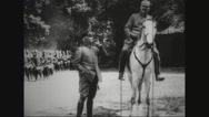 Military band marching past two military officers Stock Footage