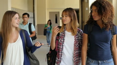 Group Of Female High School Students Walking Along Hallway Stock Footage