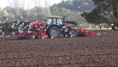Farming agriculture tractor tiling and sewing seed in field Stock Footage