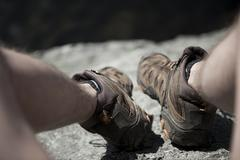 Hikers Boots On Top of Cliff Looking Down - stock photo
