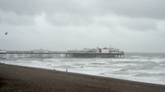 People walk on Brighton beach on a stormy day Stock Footage